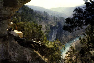 Looking out from beneath a large outcropping, to a lone hiker standing on a rock ledge below. In the distance below, a green river cuts its way through a narrow canyon, stretching off to the forest beyond.