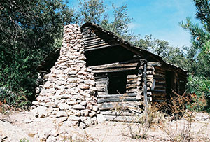 Old sagging cabin with a large stone chimney