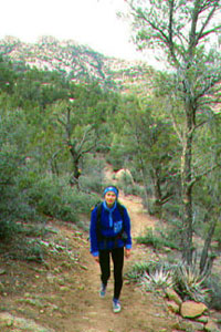 A hiker in a blue jacket treks along a dry dirt trail surrounded by trees and other shrubbery.