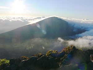 A photo from atop a peak in the Haleakala Wilderness. Clouds gather at the peaks of the mountains in this area while the sun casts its bright rays on the peaks.