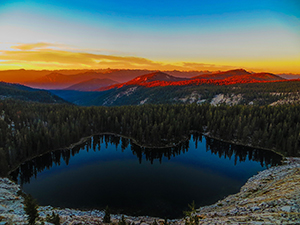 View looking down into a deep blue lake with a rainbow colored sunset in the background