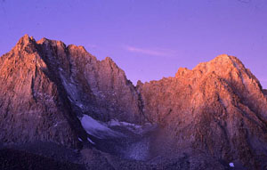 Early morning Alpenglow casts pink and purple rays on the tops of sharp rocky peaks.