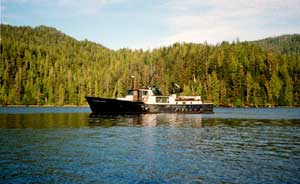 A large black boat, traveling up the shoreline, with forest hills in the background.