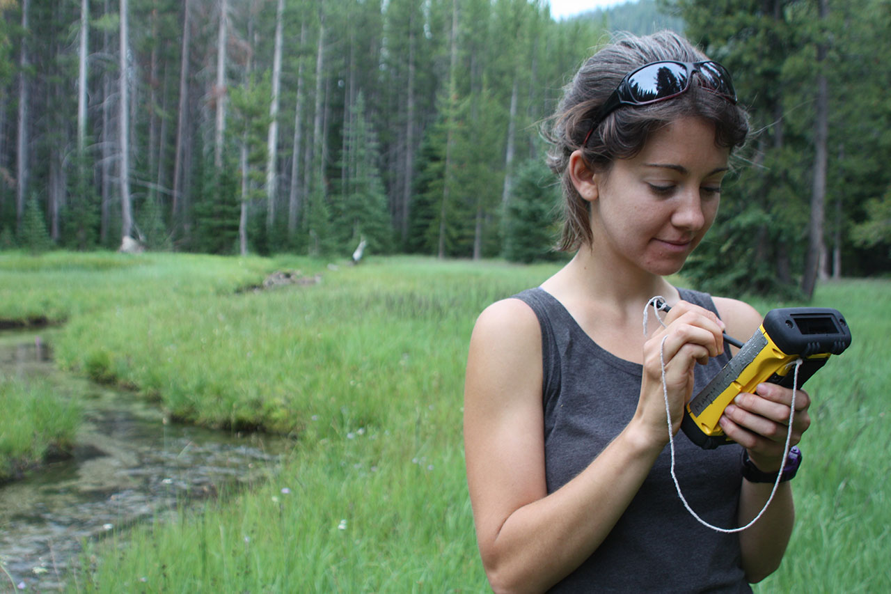 A citizen science volunteer keys data into a GPS unit