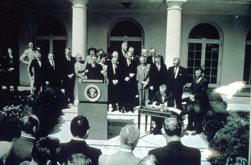 A black and white image of President Johnson, surrounded by a group of dignitaries, signing the wilderness act into action.