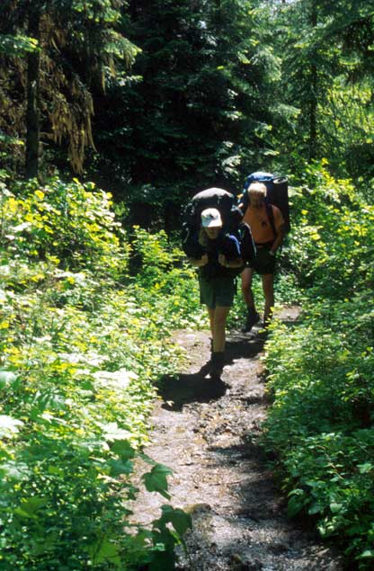 Two backpackers trudging up a narrow trail through dense green forest.