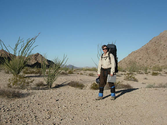 Backpacker in Mohawk Valley. The sky is free of clouds and the desert shrubs sprout up from the flat area.