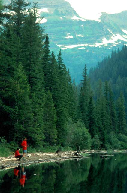 Two campers in bright red jackets standing along the shore of a placid lake. Tall vertical rock faces laced with snow rise above the forest in the background.