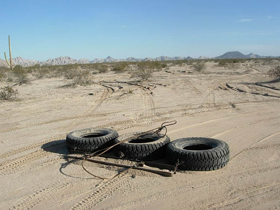 Three tires are attached together and drug behind border patrol vehicles to smoothe out the road.