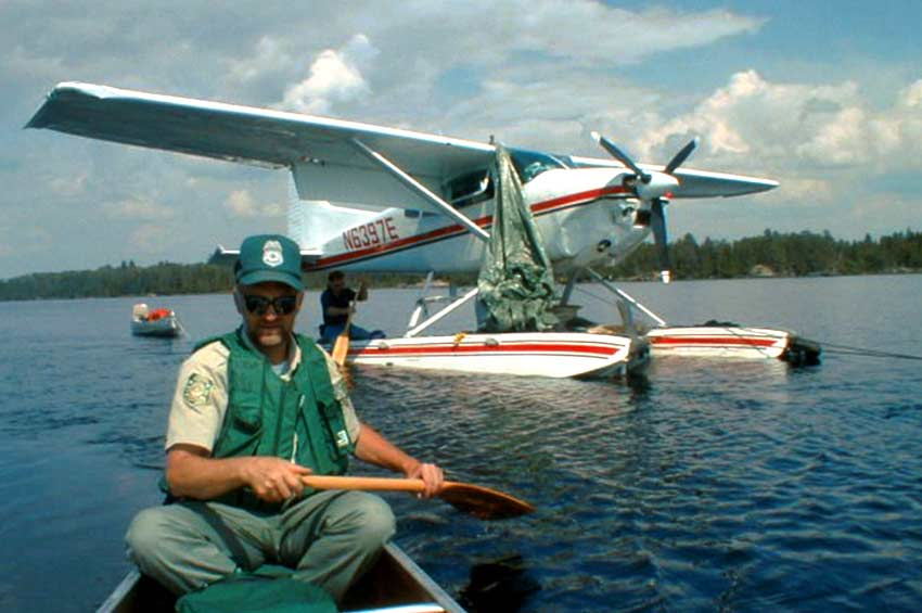 Looking back at a man in a green life vest paddling a canoe, a floatplane in the background being towed across a lake.