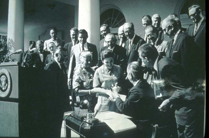 A vintage black and white image of a group of dignitaries surrounding President Johnson after the signing of the Wilderness Act.