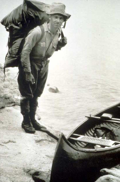 A vintage black and white image of Arthur Carhart with a large pack, standing next to a canoe.