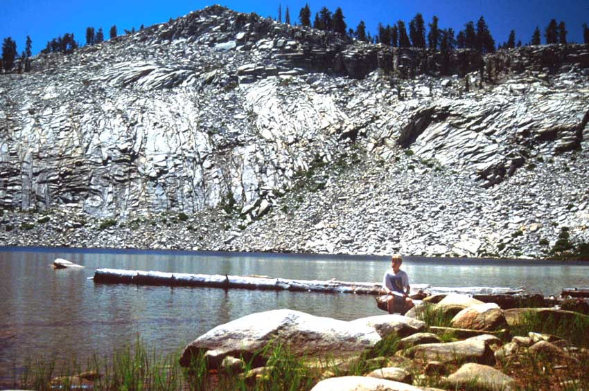 A person sitting along the edge of a small lake, a scaly white cliff rising on the far side of the water.