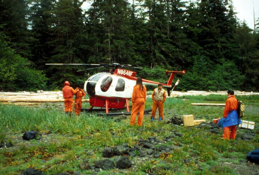 Five people in orange jumpsuits standing around a small red and white helicopter.