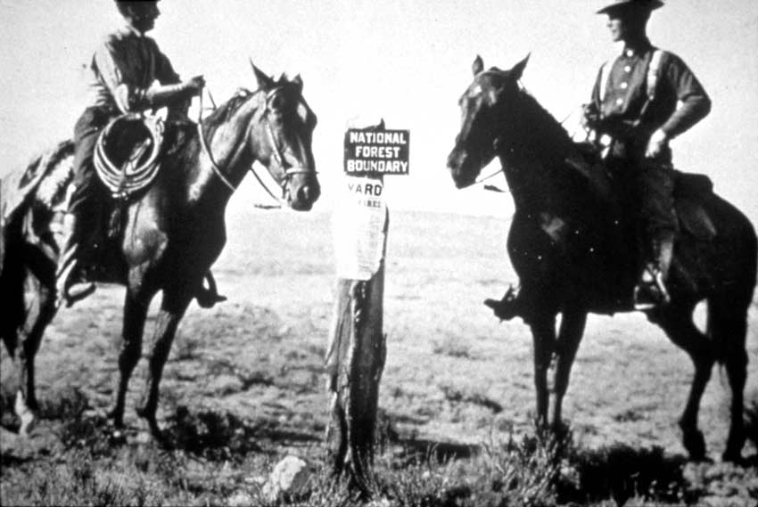 A vintage black and white image of two men on horseback, standing next to a boundary marker.