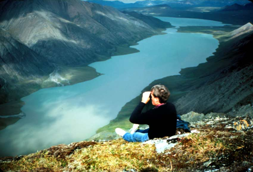 A man sitting high on a hillside with binoculars, viewing out over a large valley with a large glacial fed lake far below.