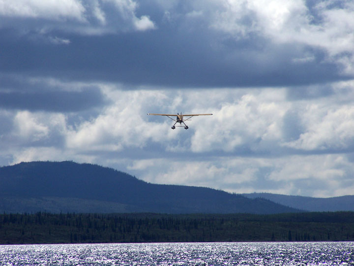 A floatplane heading towards stormy clouds, moments after lift-off from a remote Alaskan lake.