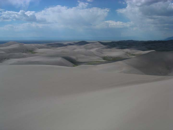 Smooth gray sand dunes roll away towards the horizon, almost mirroring the puffy clouds dotting the blue sky above.