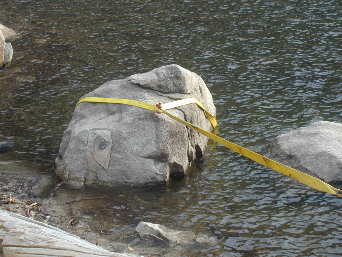 A large boulder sitting in shallow water, tied with a large yellow tow strap, for removal.