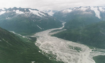 An aerial view, looking down over a massive braided river, flowing from between giant green mountains topped with glaciers.