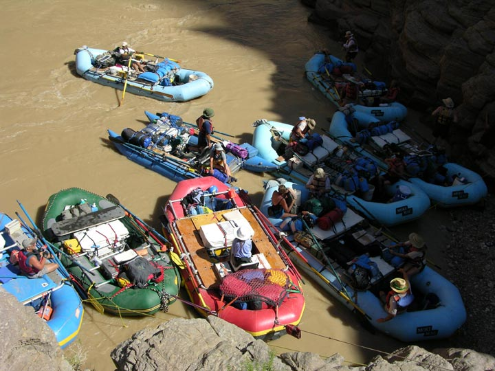 A group of rafters crowd about the edge of the Grand Canyon National Park, on the muddy waters of the river.