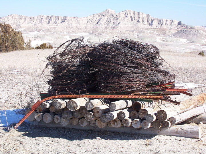 A large pile of rusty barbed wire and fence posts (removed from the wilderness), with jagged mountains in the background.