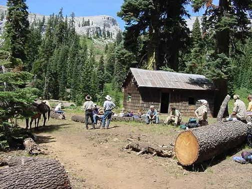 A well traveled trail leads to an open area in front of a cabin where a group of people have gathered. Some poeple sit on large logs and few of them stand. The sky is clear and sunny. Surrounding the people are sparse hills and coniferous trees.
