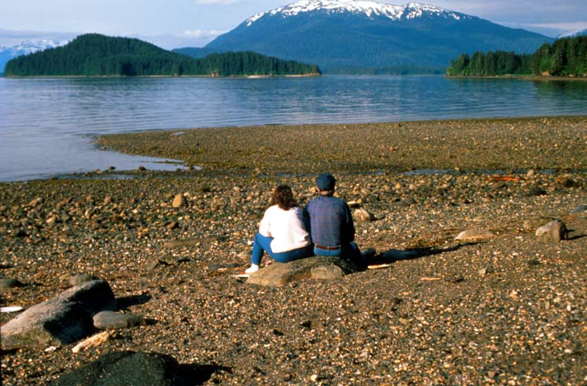 A man and a woman sit together on a large rock along the beach, overlooking a small bay. Several small islands dot the water, bordered by a large snowcapped peak beyond.