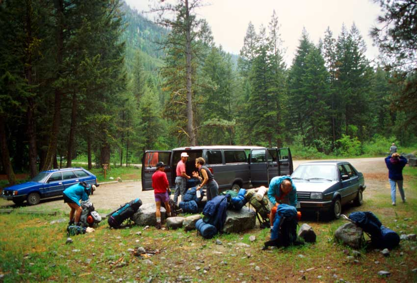 A small group of hikers unloading gear from a van, at a trailhead in the forest.