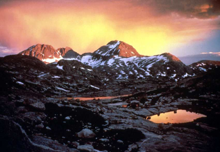 An alpine landscape under dark shadow, golden light reflecting off several small ponds and high mountain faces.