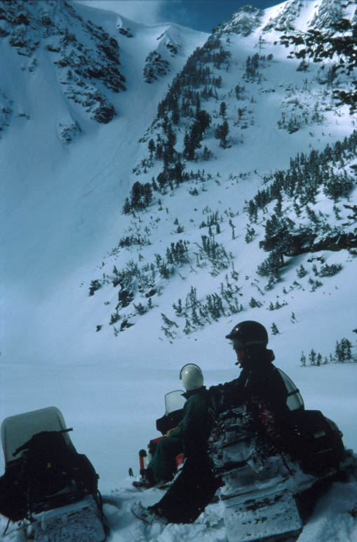Several snowmobilers in a high alpine valley, sitting at the base of a steep mountain face.