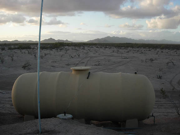 A fiberglass drinker tank sits in the foreground of the photo. In the background, the desert landscape spreads out to mountains in the distance at either sunrise or sunset.