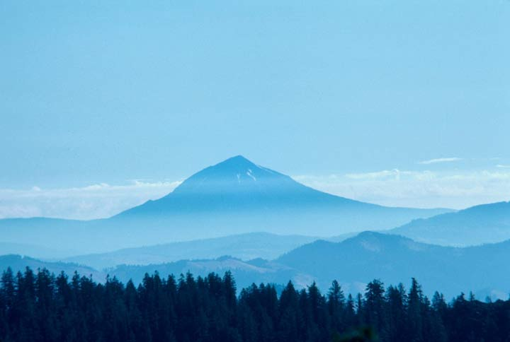 A massive peak in the distance partially obscured by a blue haze, rising above dense forested hills in the foreground.