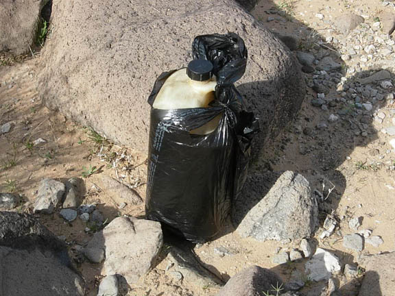 A discarded water jug wrapped in a black plastic bag. Drug smugglers will sometimes wrap their water jugs in black plastic so they don't refect moonlight and are therefore not as easily seen. Taken inside Cabeza Prieta National Wildlife Refuge.