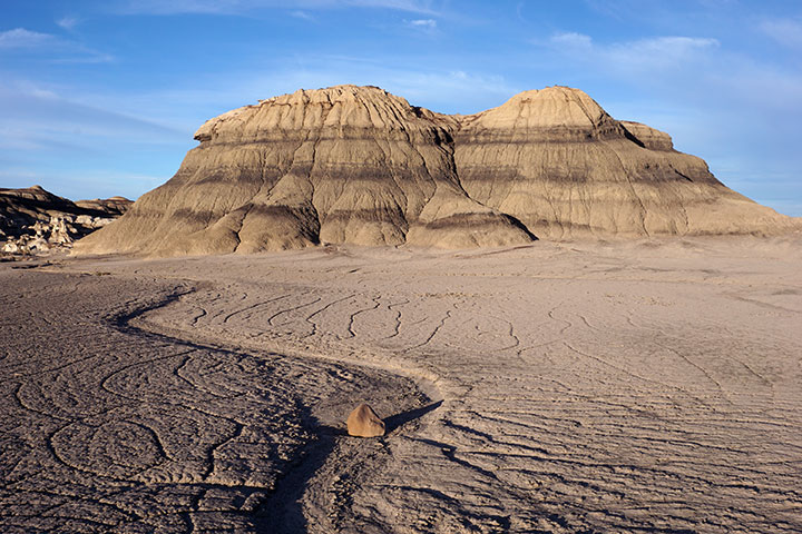 Cracking pink desert mud with a brown and tan layered badlands rock formation in the background