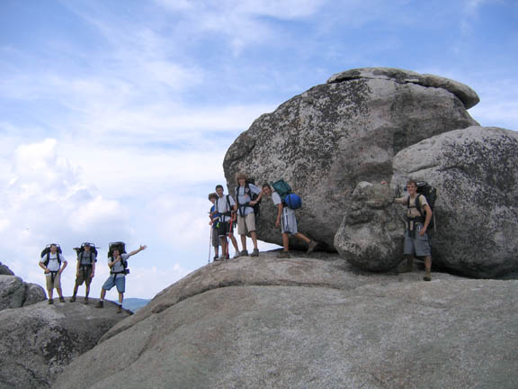 Backpackers pose next to huge boulders on a partly cloudy day at Old Rag Mountain.