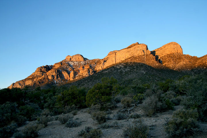 Bathed in the last rays of evening light, a low mountain rises over the shadowed desert landscape.