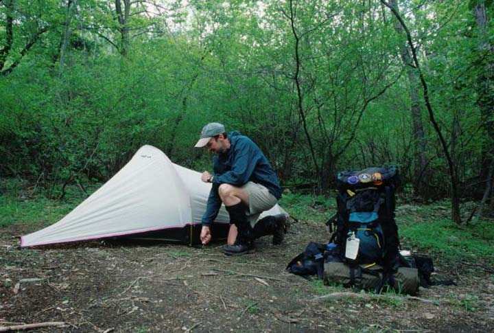 A backpacker leaves his backpack nearby as he pitches a small one-man tent at a campsite nestled in lush green vegetation.