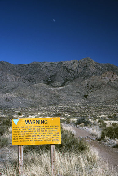 Climbing warning sign, Organ Mountains Wilderness Study Area at sunset.