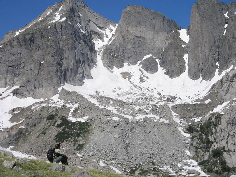 A lone hiker on a grassy slope, looking up at three vertical pinnacles of gray rock laced with snow, towering high above.