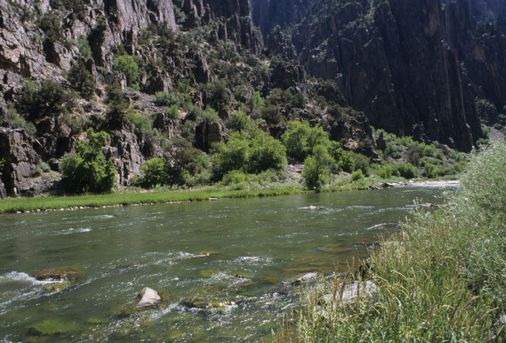 A clear river flowing along green grassy banks with the canyon walls rising on the far side.