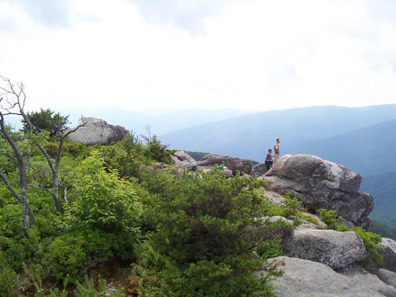 A photo from atop the grey boulder formation at Old Rag Mountain. Two hikers stand on top of the grey boulder formation.