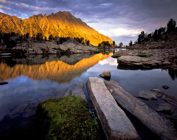 Sunlight on a mountain at the edge of a lake with large rocky boulders.