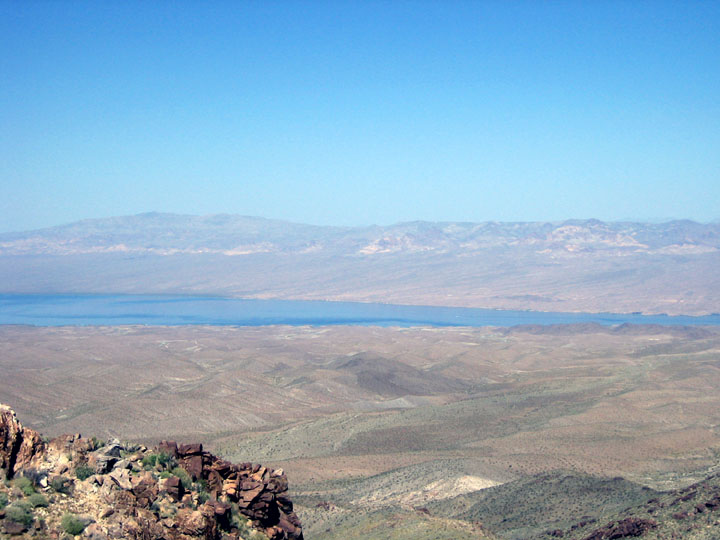 Looking out over a rocky outcropping towards the desert valley far below. A blue body of water is visible in the distance.