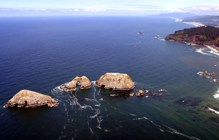 An aerial view of the Three Arch Rocks, breaking through the surface of the dark water, and the nearby coastline.