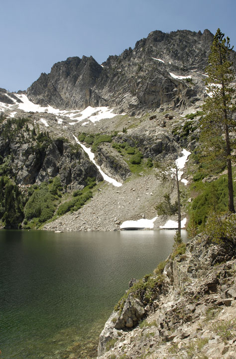 Looking out over a deep green alpine lake to a rugged mountain peak rising from the far shore.