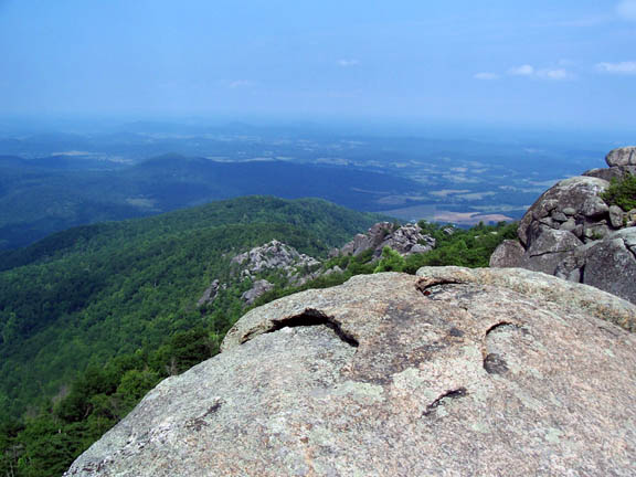A photo taken from atop the grey boulder formation at Old Rag Mountain captures the rolling green hills and hazy landscape below.
