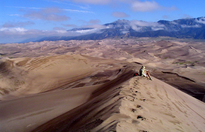 A lone hiker sits looking out over an expanse of golden sand dunes under a blue sky, with tall mountains rising out of the dunes in the distance.