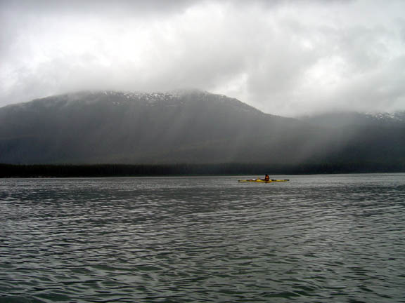 A kayak ranger, looking very small and minuscule, paddles along in the Tracy Arm of the Tracy Arm - Ford's Terror Wilderness. The clouds spit water in the mountains behind the kayaker.