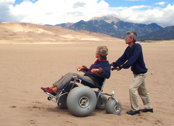 A man pushing a woman through the sand on a special wheelchair with oversized balloon tires.